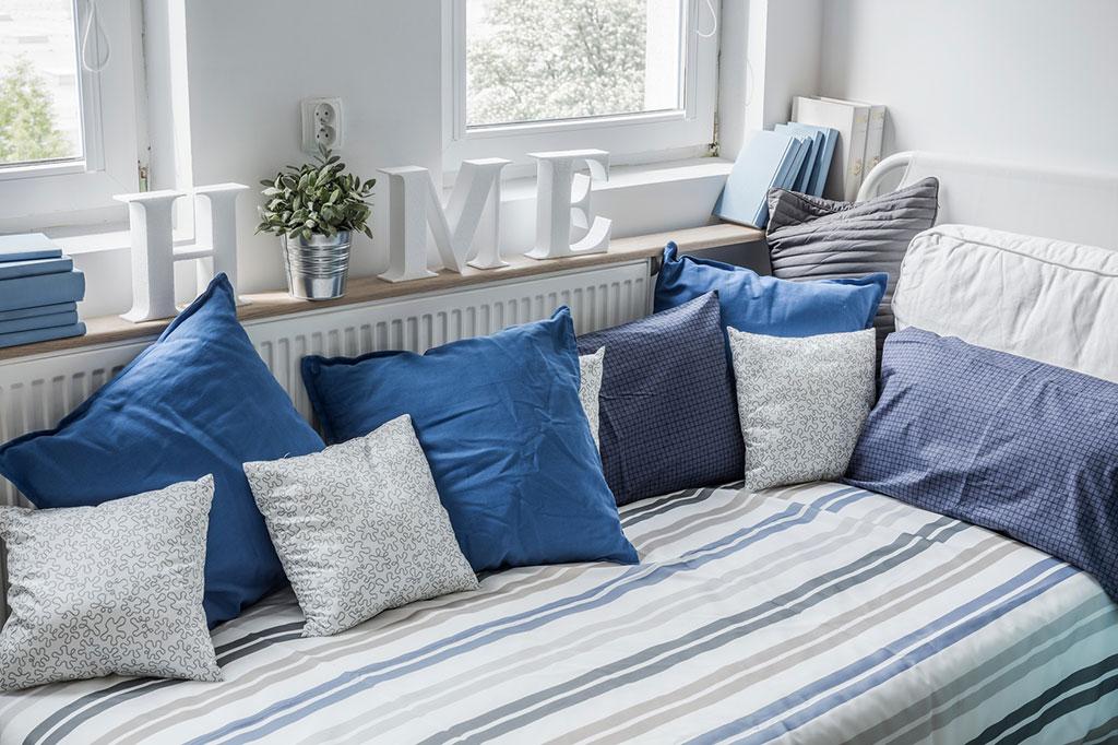 Weiss und Blau ergeben einen frischen maritimen Look. Einfach Kissen und Decken mit Streifen, Punkten oder grafischen Mustern kombinieren.